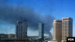 Asap tampak mengepul di Tripoli bagian barat setelah terjadi bentrokan antara pasukan NTC Libya dan pendukung Gaddafi (14/10).