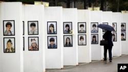 Seorang perempuan melihat karikatur para korban kapal feri Sewol yang tenggelam, di altar memorial di Ansan, Korea Selatan (16/4). (AP/Lee Jin-man)
