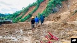 Penduduk desa mengarungi lumpur setelah tanah longsor membanjiri sebuah desa di distrik Phuoc Loc, provinsi Quang Nam, Vietnam Kamis, 29 Oktober 2020. (Foto: AP)