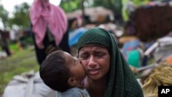 A Rohingya Muslim child kisses his mother's cheek as they rest after having crossed from Myanmar to the Bangladesh side of the border near Cox's Bazar's Teknaf area, Sept. 2, 2017. Tens of thousands have crossed into Bangladesh in the last 24 hours as the