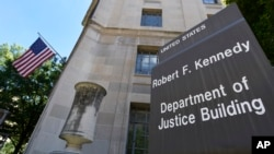 FILE - A sign is seen in front of the United States Justice Department in Washington, Aug. 27, 2015.