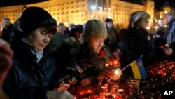 Ukrainians light candles during a rally in Kyiv, Ukraine, Friday, Nov. 21, 2014.