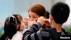 1月23日在香港西九龍高鐵火車站,一名婦人戴上口罩。