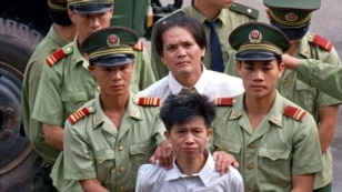 Men convicted of drug related crimes hear the public announcement for their death sentences in Shenzhen, China, on August 15, 1996.  (AP Photo/Vincent Yu, File)