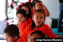 Migrant children take English lessons at a bus converted in a classroom as part of Schools On Wheels program by California's 'Yes We Can' organization, in Tijuana, Mexico August 2, 2019.
