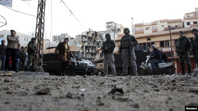 Residents and Lebanese army soldiers inspect damage following days of clashes between Sunni Muslims and Alawites in the port-city of Tripoli, northern Lebanon, December 10, 2012.