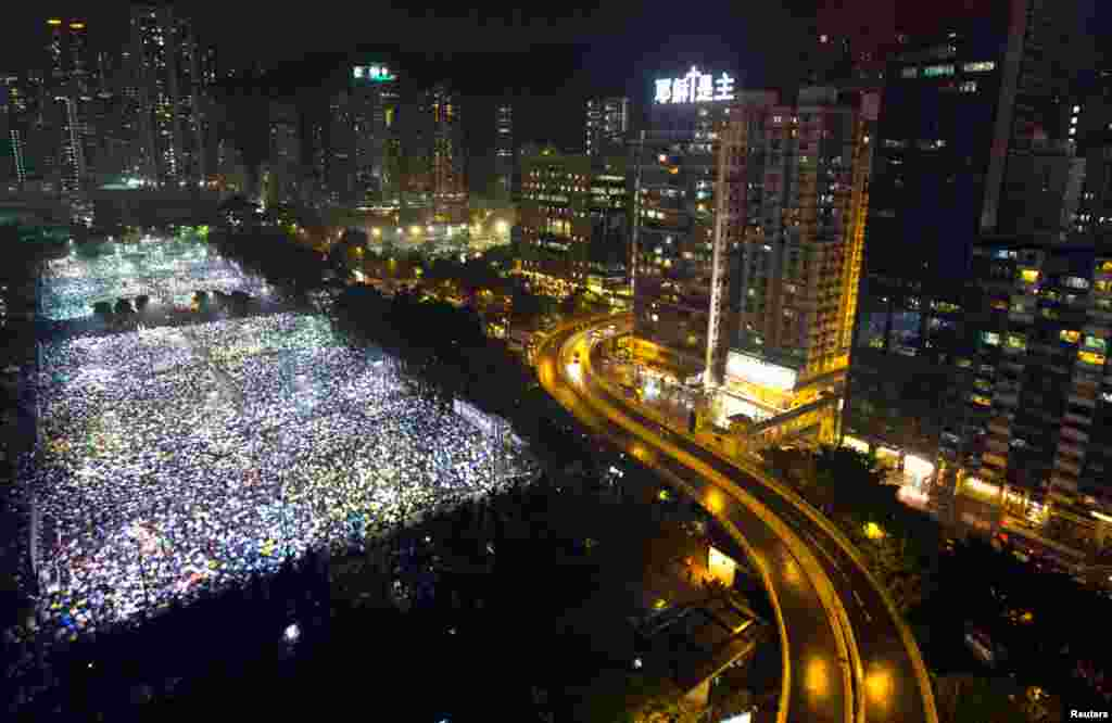 Tens of thousands of people attend a candlelight vigil under heavy rain at Victoria Park in Hong Kong, June 4, 2013 to mark the 24th anniversary of the Chinese military crackdown on the pro-democracy movement in Beijing.