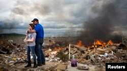 Michael Stanek hugs his daughter Kennedy Stanek as they take a break from helping friends sift though the rubble of their homes in Vilonia, Arkansas, April 30, 2014.
