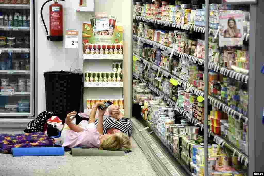 گرمای هوا در هلسینکی فنلاند موجب شده این خواربار فروشی به عابران گرما زده اجازه دهد دقایقی در زیر کولر استراحت کنند.