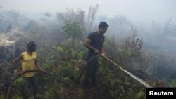 Orang-orang berusaha memadamkan kebakaran hutan di Bengkalis, Riau (21/10/ 2010), yang disebabkan oleh pembakaran hutan untuk pembukaan lahan.