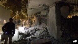 这张利比亚政府组织的参访时拍摄的照片显示,官员和媒体记者在查看被北约导弹攻击后的受损的房子。