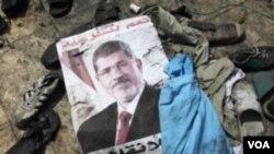ຮູບໂພສເຕີ ຂອງອະດີດ ປະທານາທິບໍດີ ອີຈິບ ທ່ານ Mohammed Morsi ຖືກພວກປະທ້ວງປະຖີ້ມໄວ້ ຢູ່ກອງຂີ້ເຫຍື້ອ.