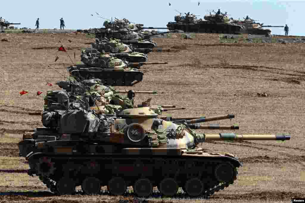 Turkish army tanks take up position on the Turkish-Syrian border near Suruc, Oct. 6, 2014.