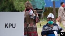 Seorang perempuan mengenakan masker dan sarung tangan plastik tengah memeriksa surat suaranya disaksikan petugas pemungutan suara dalam PIlkada di sebuah TPS di Medan, Sumatera Utara, 9 Desember 2020. (AP Photo/Binsar Bakkara)