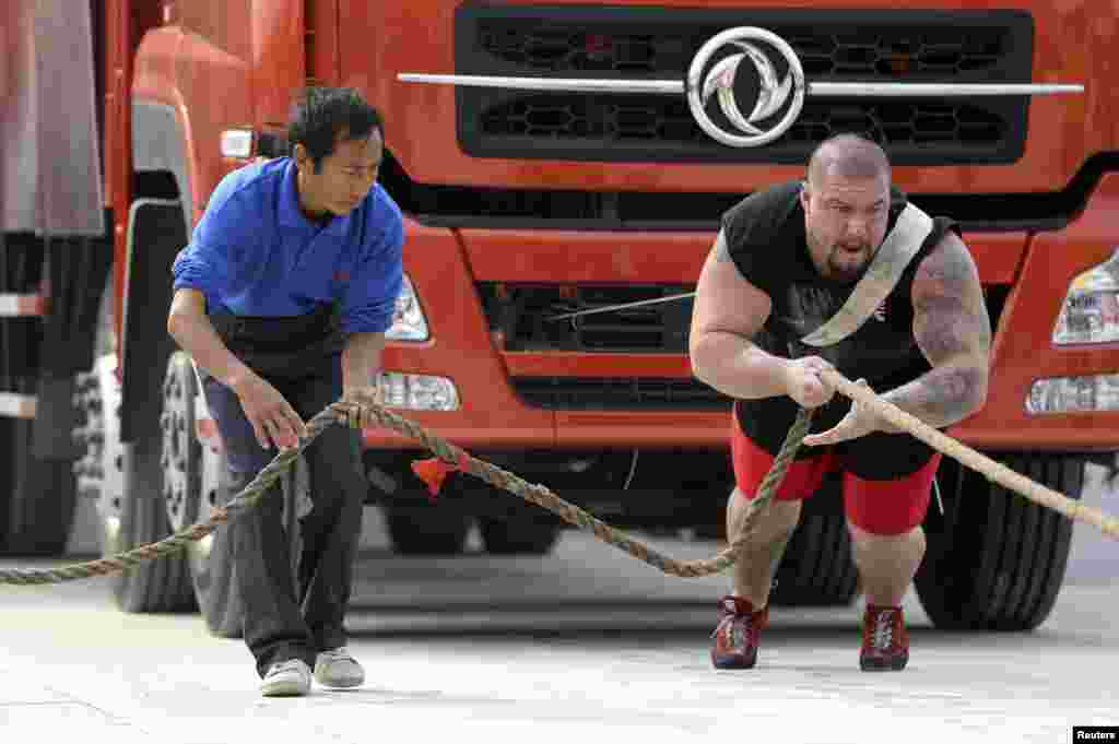 British participant Kenneth Nowicki (R) drags a truck during the annual Chinese Hercules Open in Xiangyang, Hubei province, China.