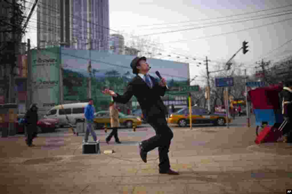 A man dances as he sings karaoke on a street in central Beijing, China, Tuesday, Feb. 21, 2012.