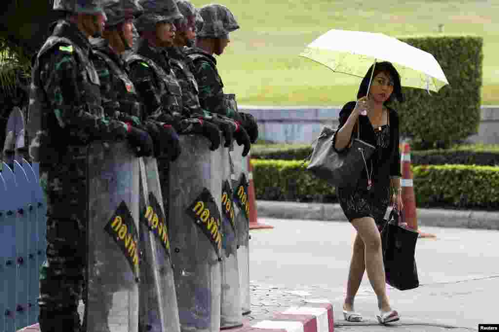 A woman walks past soldiers providing security to the Army Club where senior army officials are meeting foreign diplomats in Bangkok, May 23, 2014.
