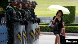 A woman walks past soldiers providing security to the Army Club where senior army officials meet foreign diplomats in Bangkok May 23, 2014. Thai army chief General Prayuth Chan-ocha set out his plans for the country on Friday, a day after seizing power in