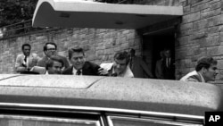 FILE - In this March 30, 1981, photo, U.S. president Ronald Reagan, center, is shown being shoved into his limousine by secret service agents after being shot by John Hinckley outside a Washington, D.C., hotel.