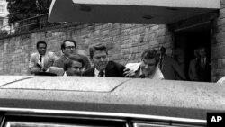 Les agents des services secrets poussent dans limousine le président Ronald Reagan, au centre, touché par une balle dont le tireur, John Hinckley Jr, a été plus tard déclaré malade mental, à Washington, Etats-Unis, 30 mars 1981.
