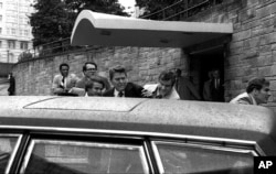 FILE - In this March 30, 1981, photo, U.S. president Ronald Reagan, center, is shown being shoved into his limousine by secret service agents after being shot outside a Washington hotel.