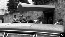 FILE - In this March 30, 1981, photo, U.S. president Ronald Reagan, center, is shown being shoved into his limousine by secret service agents after being shot outside a Washington hotel. The man who shot Reagan is scheduled to leave a Washington mental ho