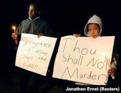 Darick Lane dan putranya Desmond Lane memegang lilin di luar penjara sebelum eksekusi John Allen Muhammad di Pusat Pemasyarakatan Greensville di Jarratt, Virginia, 10 November 2009. (Foto: REUTERS/Jonathan Ernst)