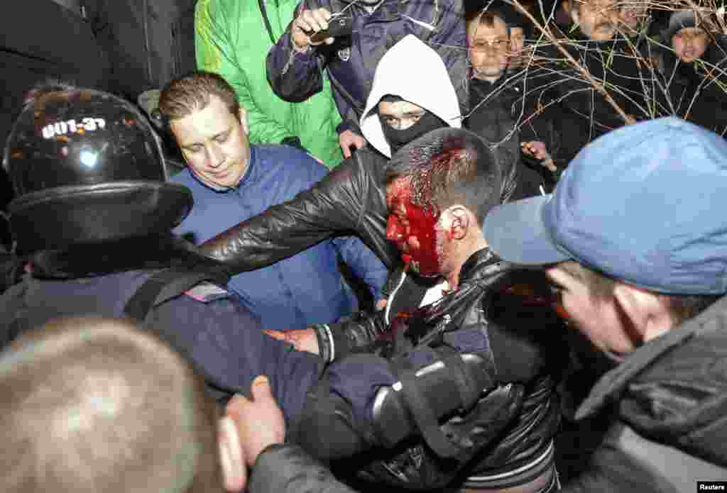 Police officers escort a wounded participant of an anti-war rally during clashes with pro-Russia demonstrators in Donetsk, Ukraine, March 13, 2014.