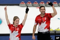Canada's Kaitlyn Lawes, left, and John Morris jubilate after winning their mixed doubles curling finals match against Switzerland at the 2018 Winter Olympics in Gangneung, South Korea, Feb. 13, 2018. Canada won the gold medal.