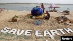 Students make a sand sculpture on the Earth Day, on the banks of the river Yamuna in Allahabad, India, April 22, 2018. REUTERS/Jitendra Prakash - RC1EA881C5B0