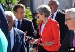 French President Emmanuel Macron, left, talks with British Prime Minister Theresa May when arriving for a family photo at the informal EU summit in Salzburg, Austria, Sept. 20, 2018.