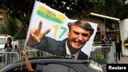 A supporter of Brazil's new president-elect, Jair Bolsonaro, celebrates in front of Bolsonaro's condominium at Barra da Tijuca neighborhood in Rio de Janeiro, Brazil, Oct. 29, 2018.