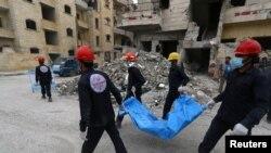 Trabajadores de rescate llevan un cuerpo en Raqqa, Siria, 9 de abril de 2018. Reuters