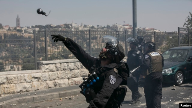 Israel police tosses a grenade towards Palestinians protesters on July 4, 2014.