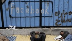 Opposition supporters rest near graffiti referring to Facebook in Tahrir Square in Cairo on Saturday