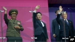 North Korean officials, including National Defense Commission Vice Chairman Hwang Pyong So, left, wave as their team marches into the stadium during the closing ceremony of the 17th Asian Games in Incheon, South Korea, Oct. 4, 2014.