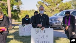 In this June 1, 2020, photo provided by the Catholic Diocese of El Paso, Bishop Mark Seitz, center, kneels with other demonstrators at Memorial Park holding a Black Lives Matter sign in El Paso, Texas. (Fernie Ceniceros/Catholic Diocese of El Paso via AP)
