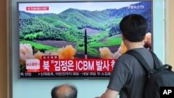 在首尔火车站,旅客观看关于朝鲜发射导弹的电视新闻(2017年7月4日)