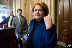 FILE - In this Jan. 22, 2018 file photo, Sen. Heidi Heitkamp, D-N.D., leaves a meeting with fellow Democrats at the Capitol in Washington.