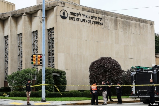 Police officers guard the Tree of Life synagogue following shooting at the synagogue in Pittsburgh, Pa, Oct. 27, 2018.