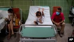 Küba'da aşı olan küçük bir çocuk bir süre gözlem altında tutulurken cep telefonuyla oynuyor.