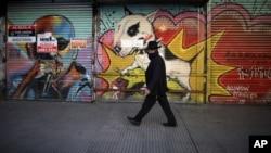 Seorang pria berjalan di kawasan pertokoan yang tutup selama masa pembatasan wilayah di tengah pandemi Covid-19 di Buenos Aires, Argentina, Jumat, 26 Juni 2020. (Foto: dok).