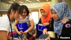 雅加达的三星公司雇员对人讲解如何使用三星手机。中国制造的三星产品广泛出口