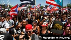 People chant slogans as they wave Puerto Rican flags during a protest calling for the resignation of Governor Ricardo Rossello in San Juan, Puerto Rico July 22, 2019. (REUTERS/Marco Bello)