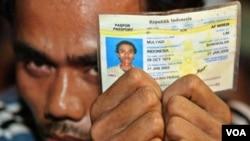 Seorang TKI asal Indonesia menunjukkan kartu tanda identiasnya sembari menunggu petugas imigrasi memeriksa dokumennya dalam sebuah razia di Klang, pinggiran Kuala Lumpur (foto: dok).