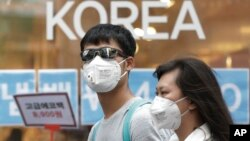 A couple wears masks as a precaution against the Middle East Respiratory Syndrome (MERS) virus as they walk in Myeongdong, one of Seoul's main shopping districts, June 15, 2015.