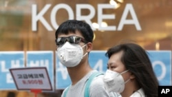 Un couple se protégeant contre le MERS en portant des masques (AP Photo/Ahn Young-joon)