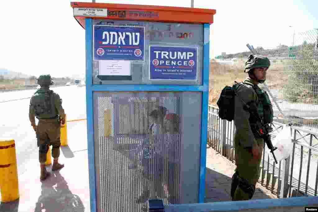 ទាហានអ៊ីស្រាអែលឈរជិតកន្លែងរងចាំរថយន្តក្រុងមួយជាមួយនឹងផ្ទាំងបដាយុទ្ធនាការឃោសនាបោះឆ្នោតគាំទ្រលោក Donald Trump នៃគណបក្សសាធារណរដ្ឋនៅសហរដ្ឋអាមេរិក ជិតតំបន់តាំងទីលំនៅ Ariel នៃតំបន់ West Bank។