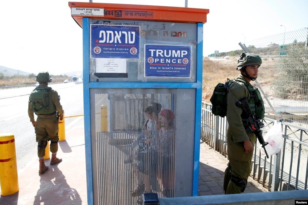 요르단강 서안 유대인 정착촌 버스 정류장에 모습을 드러낸 이스라엘군 병사들. 정류장 벽에 미 공화당 현지 지부가 붙여놓은 도널드 트럼프 지지 포스터가 눈에 띈다.