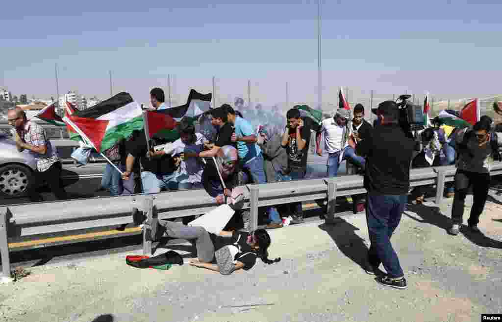 Palestinian protesters run as Israeli border policemen fire a stun grenade during a demonstration to show solidarity with Bedouin citizens, near the West Bank village of Hizma, south-east of Ramallah. Some 60 protesters demonstrated against an Israeli cabinet plan to relocate some 30,000 Bedouin citizens who live in unrecognized villages in Israel's southern Negev desert and relocate them to towns built by the government.